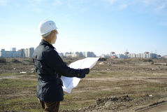 Women architect on site. Architect with blueprints and hard hat at site Royalty Free Stock Photography