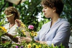 Women arranging flowers outdoor greenery Stock Photo
