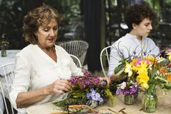 Women arranging flowers together outdoor Stock Photography
