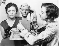 Women and an artist standing together while one is working on a bust stock photography