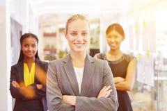 Women as business team. Smiling interracial women as business team in start-up company stock photos