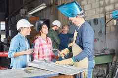 Women as trainees in welder apprenticeship. With instructor stock photography