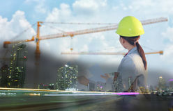 Women asia engineer working and holding blueprints at constructi Stock Photos