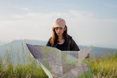 Women asian with bright backpack looking at a map. View from bac. K of the tourist traveler on background mountain Royalty Free Stock Photography