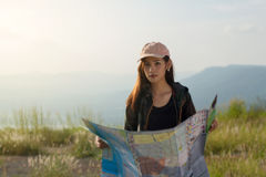 Women asian with bright backpack looking at a map. View from bac. K of the tourist traveler on background mountain Stock Photo