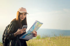 Women asian with bright backpack looking at a map. View from bac. K of the tourist traveler on background mountain, Female hands using smartphone, holding gadget Stock Photo