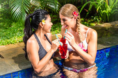 Women at Asian hotel pool drinking cocktails Stock Photo