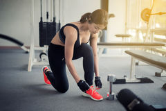 Women asian tying shoe laces. fitness women getting ready for en. Women asian tying shoe laces. fitness woman getting ready for engage in the gym Stock Image