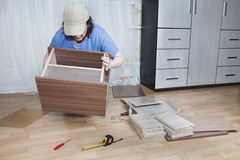 Women Assembling flat pack furniture  on floor in living room. Royalty Free Stock Photos