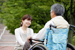 Women assisted wheelchair royalty free stock images