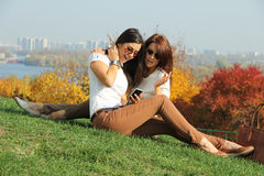 Women with autumn maple leaves in park Royalty Free Stock Photo