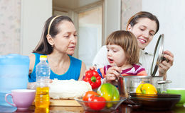 Women with baby girl cook with vegetables Stock Images