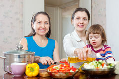 Women with baby girl cook veggie lunch Stock Photography