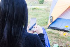 Women back or rare view playing game or use smartphone or mobile. Phone with blurred tent and garden background Royalty Free Stock Photos
