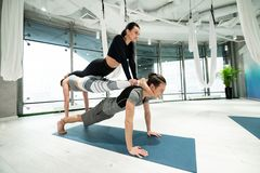 Man holding two women on his back while practicing fitness yoga. Women on back. Strong men holding two slim and fit women on his back while practicing fitness royalty free stock images