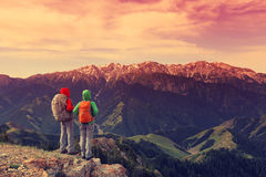 Women backpackers enjoy the view on mountain peak cliff. Two successful women backpackers enjoy the view on mountain peak cliff royalty free stock image