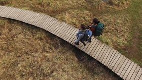 Women Backpackers Walking On The Path. Aerial: Two Women Backpackers Walking On The Path At Summer stock video