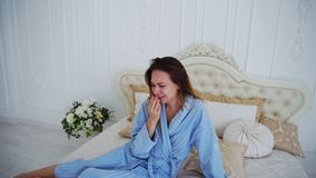 Women in Bad Mood, Upset and Crying, Sitting on Bed in Spacious Bedrooms. Girl Sits on Beautiful Double Bed and Sad, Crying Because of Failed Plans or Bad Day royalty free stock photo