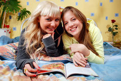 Women at the badroom. Two beautiful women reading magazine at the badroom stock photography