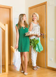 Women with bags of food near door Royalty Free Stock Photos