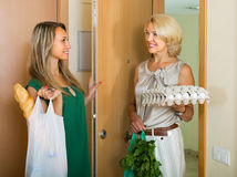 Women with bags of food near door Stock Photography