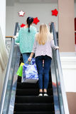 Women with bags on the moving staircase Stock Photos