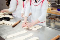 Women bakers make buns from dough.  stock photography