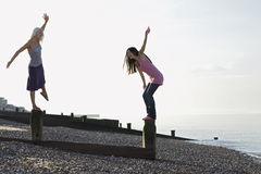 Women Balancing On Wave Breakers At Beach Royalty Free Stock Photos