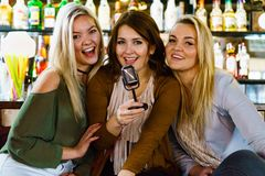 Women in bar singing karaoke royalty free stock photo