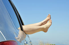 Women with bare feet out the window of the car Stock Photography