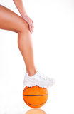 Women bare legs and basket ball. Women bare legs and sneakers with basket ball Stock Photography