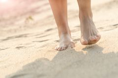 Women barefoot walking on the white sand nature on the beach. summer trip Royalty Free Stock Photo
