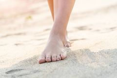 Women barefoot walking on the white sand nature on the beach. summer trip Stock Photo