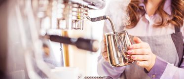 Women Barista using coffee machine for making coffee in the cafe stock photo