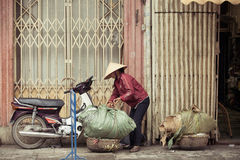 Women with baskets on the street of Hanoi, Vietnam. Hanoi, Vietnam - 3 MARCH: Women with baskets on the street of Hanoi, March 3, 2014 Royalty Free Stock Photos