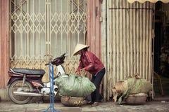 Women with baskets on the street of Hanoi, Vietnam. Royalty Free Stock Photos