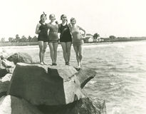 Women in bathing suits posing on rock Stock Image