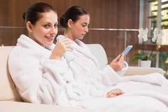 Women in bathrobes drinking water and text messaging Royalty Free Stock Image