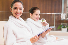Women in bathrobes drinking water and text messaging Royalty Free Stock Images