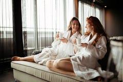 Women in bathrobes enjoying tea stock image