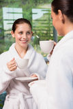 Women in bathrobes having tea. Two smiling young women in bathrobes having tea Royalty Free Stock Photo
