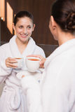 Women in bathrobes having tea. Two smiling young women in bathrobes having tea Royalty Free Stock Image
