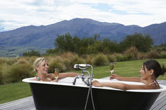 Women In Bathtub With Champagne Against Mountains Stock Image
