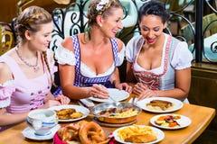 Women in Bavarian pub eating food for dinner Royalty Free Stock Photo