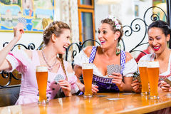 Women in Bavarian pub playing cards. And a game of Schafkopf royalty free stock photos