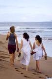 Women on the Beach. Three women walking along a windy beach in Hawaii stock photo