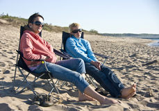 Women on beach. Two women sitting on beach chairs. Late afternoon day, spring Royalty Free Stock Images