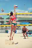 Women beach volleyball players. Woman jumping doing spike Royalty Free Stock Image