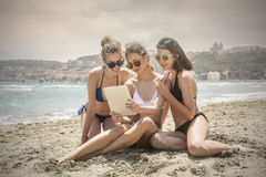 Women at the beach. Watching something on a tablet Stock Photography