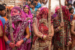 Women beat up men with long sticks as a ritual in the Lathmar Holi celebration in Nandgaon. Nandgaon, India - March 18, 2016: Women beat up men with long sticks stock images